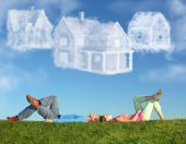 stock photo of dream home  - lying couple on grass and dream three cloud houses collage - JPG