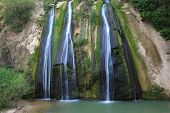 Unusual three-jet waterfall. Three parallel stream running down the steep slope and fall into the ov