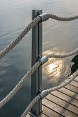 Banister with thick ropes over calm water