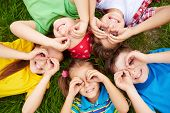 foto of youngster  - Group of cute children lying on grass  - JPG