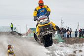 Jump of sportsman on snowmobile