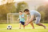 stock photo of football  - Young father with his little son playing football on football pitch - JPG