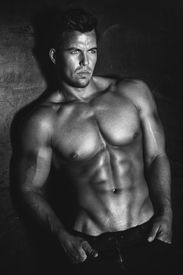 image of hunk  - Sexy fashion portrait of a hot male model with muscular body posing in studio looking at camera - JPG