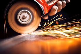 stock photo of sparking  - Worker cutting metal with grinder. Sparks while grinding iron ** Note: Shallow depth of field - JPG