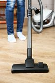 Woman with vacuum cleaner in room
