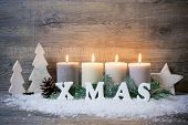 Rustic Christmas background with four advent candles burning