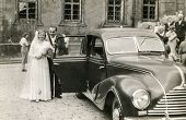 POLAND, CIRCA FIFTIES: Vintage photo of newlyweds with an old car
