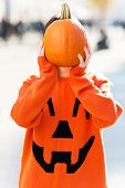 Woman holding a pumpkin in front of face