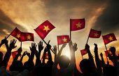Group of People Waving Vietnamese Flags in Back Lit