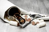 Corks, corkscrew and wine bottle on a wooden  background