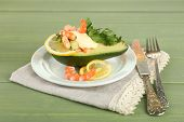 Tasty salad with shrimps and avocado on plate, on wooden background