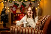 Cute Smiling Woman Holding Cup Of Tea At Fireplace