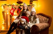 Mother And Two Daughters Sitting On Sofa At Fireplace At Christmas Eve