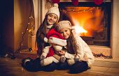 Toned Photo Of Two Happy Girls Sitting With Toy At Fireplace On Christmas Eve