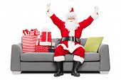 Santa gesturing happiness seated on sofa with gifts isolated on white background