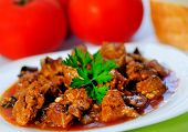 picture of stew  - Plate with stew of pork meat on table - JPG