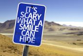 It's Scary What a Smile Can Hide sign with a desert background