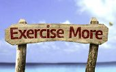 Exercise More sign with a beach on background