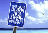 You Were Born To Be Real Not To Be Perfect sign with a beach on background
