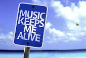 Music Keeps Me Alive sign with a beach on background