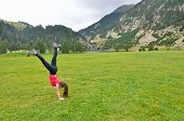 Teenage Girl Doing Acrobatics In Front Of A Lake