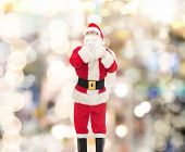 christmas, holidays and people concept - man in costume of santa claus with bag making hush gesture over lights background