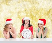 christmas, winter, holidays, time and people concept - smiling women in santa helper hats with clock over yellow lights background