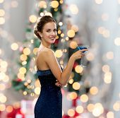 party, drinks, holidays, people and celebration concept - smiling woman in evening dress holding cocktail over christmas tree lights background