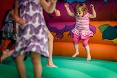 stock photo of castle  - Cute little girl jumping inside the inflatable bouncy castle - JPG