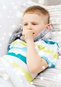 childhood, healthcare and people concept - ill boy with scarf lying in bed and coughing at home