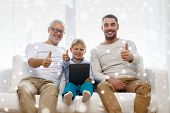 family, generation, technology and people concept - smiling father, son and grandfather sitting on couch with tablet pc computer showing thumbs up gesture at home