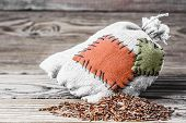 foto of thrift store  - Concept of the thrift storing - Red rice in the burlap sack with the patch on a wooden background