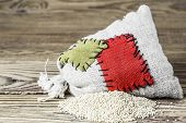 Concept of the thrift storing - Quinoa in the burlap sack with the patch on a wooden background