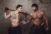 Strong and tattooed men with pitchfork