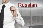 pic of pronunciation  - businessman in office room writing russian in the air - JPG