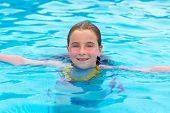 Blond kid girl swimming in the pool with sun tan red cheeks