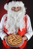 Closeup shot of Santa Claus serving a fresh baked Apple Pie. Santa is holding the dessert in both hands in front of his torso. Vertical format over a light to dark red background.
