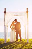 Tropical Sunset Wedding by the Ocean, Bride and Groom on Wedding Day.