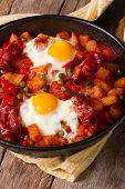 Fried Eggs With Chorizo And Vegetables In The Pan. Vertical