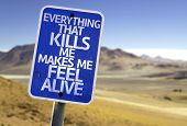 Everything That Kills Me Makes Me Feel Alive sign with a desert background