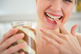 image of finger-licking  - Closeup on happy young woman licking chocolate butter from finger  - JPG
