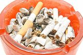 stock photo of butts  - butts in red ashtray on white closeup - JPG