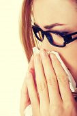 stock photo of blowing nose  - Sick young woman blowing her nose - JPG