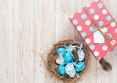 stock photo of nesting box  - Easter with blue and white eggs in nest and gift box over white wood - JPG