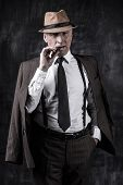 stock photo of suspenders  - Serious senior man in hat and suspenders smoking cigar and looking at you while standing against dark background - JPG
