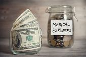picture of coins  - Dollars and coins in glass jar with medical expenses label - JPG