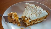 picture of pumpkin pie  - Slice of whipped pumpkin pie with a fork full in front - JPG