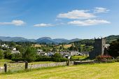 image of english rose  - Beautiful English country village of Hawkshead Lake District Cumbria UK in summer with blue sky church and pink roses - JPG