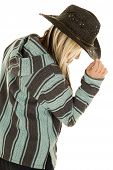 stock photo of cowgirls  - A cowgirl with her face hidden reaching up and touching the brim of her hat - JPG