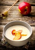 picture of porridge  - porridge with caramel apples in a bowl on a wooden table - JPG